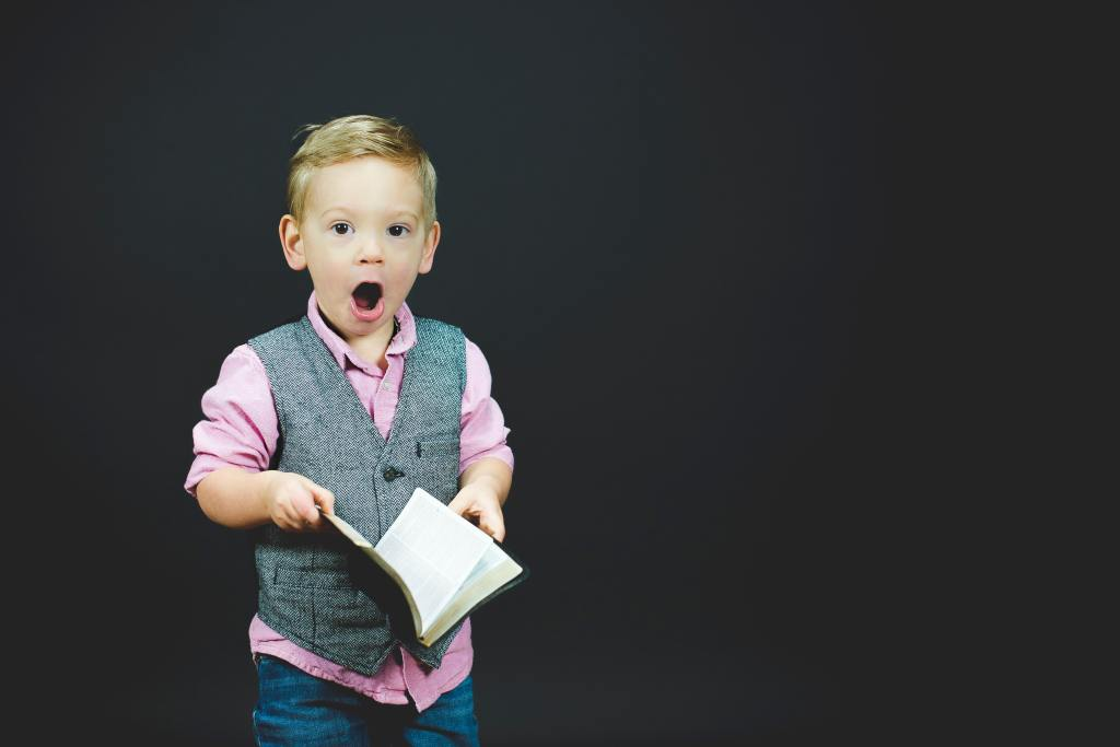 little boy holding book with surprised expression